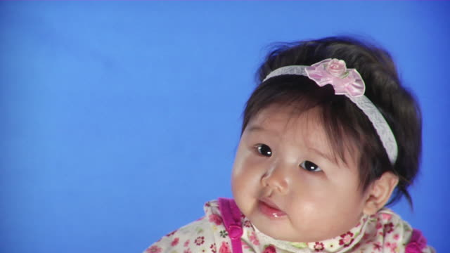CU Studio shot of baby girl (6-11 months) on blue screen