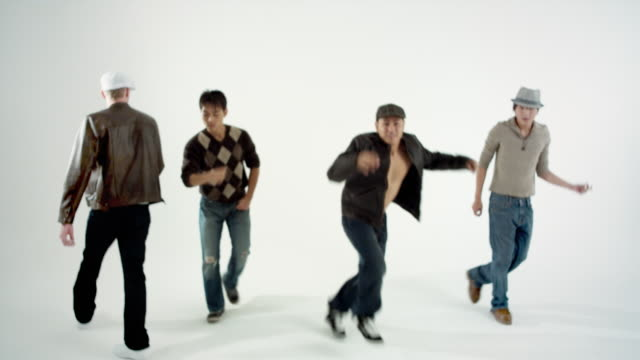 ms studio shot of boy band dancing and singing - kleine personengruppe stock-videos und b-roll-filmmaterial