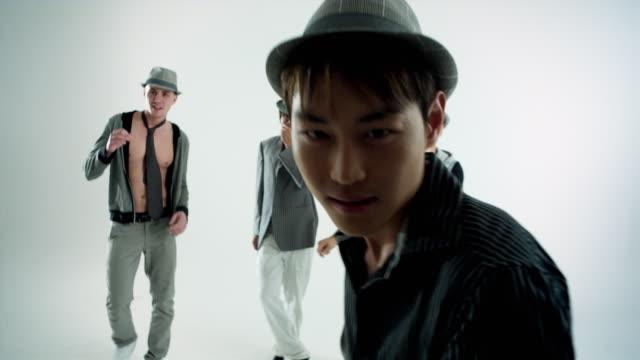 MS Studio shot of boy band dancing, man in foreground singing