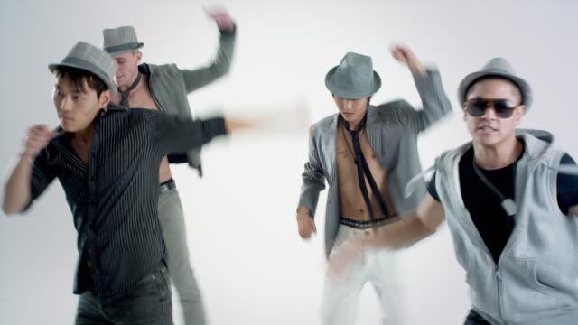 MS Studio shot of boy band dancing