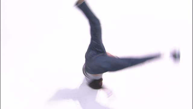 WS HS Studio shot of boy (14-15) break dancing, turning on head / Orem, Utah, USA