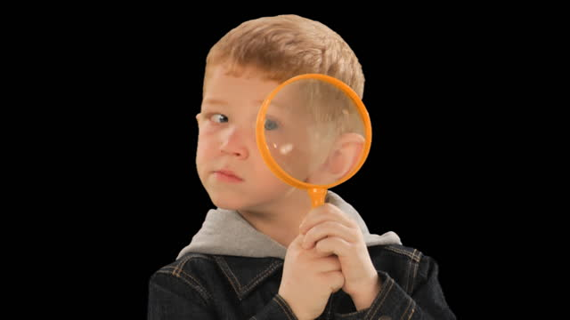 cu, studio shot of boy (6-7) looking through magnifying glass - looking through an object stock videos and b-roll footage