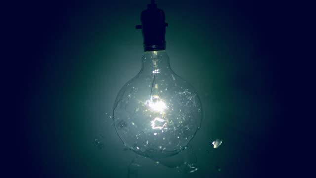 SLO MO MS Studio shot of bullet shattering light bulb against blue background