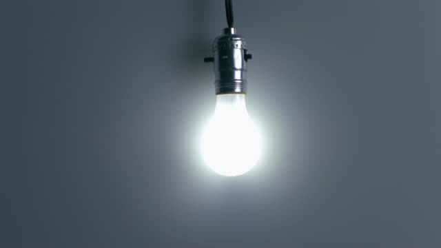 SLO MO MS Studio shot of bullet shattering light bulb against blue background