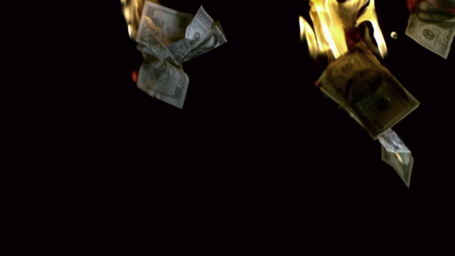 vidéos et rushes de slo mo ms studio shot of burning dollar bills falling on black background - billet de banque
