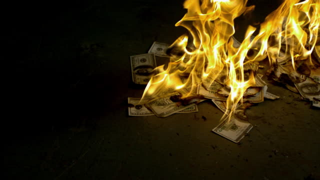 SLO MO MS Studio shot of burning dollar bills on black background