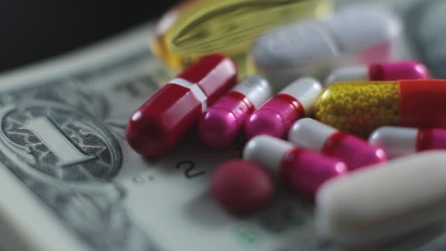 cu focusing studio shot of capsules on stack of dollars - capsule medicine stock videos & royalty-free footage