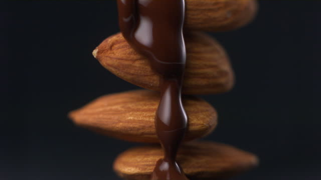 cu studio shot of chocolate being poured on stack of almonds - nut food stock videos & royalty-free footage
