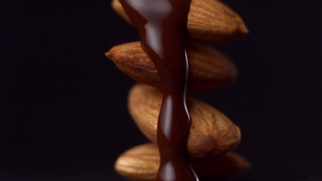 CU Studio shot of chocolate being poured on stack of almonds