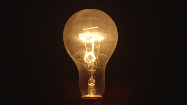 cu studio shot of clear incandescent light bulb - イルミネーション点の映像素材/bロール
