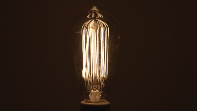 cu studio shot of clear incandescent light bulb - incandescent bulb stock videos and b-roll footage