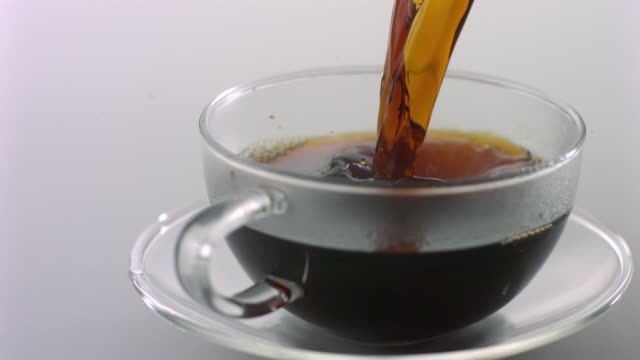 SLO MO MS Studio shot of coffee being poured into glass coffee cup