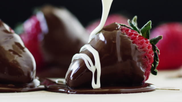 CU Studio shot of cream being poured on chocolate dipped strawberry