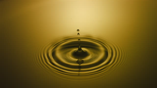 SLO MO CU Studio shot of drop falling into golden water