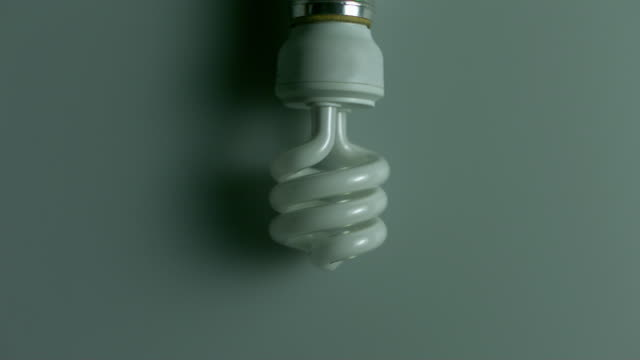 ms studio shot of energy saving light bulb glowing against green background - energy efficient stock videos & royalty-free footage
