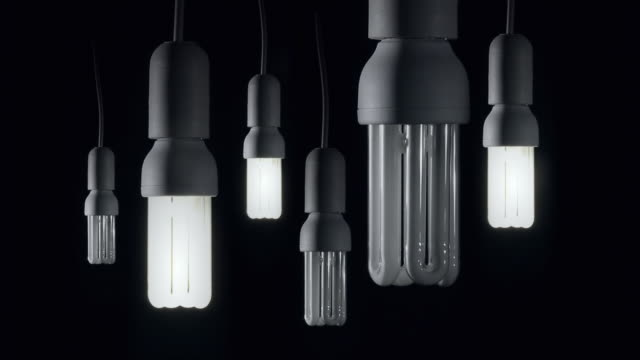 ms studio shot of energy saving light bulbs illuminated against black background / germany - energy efficient stock videos & royalty-free footage