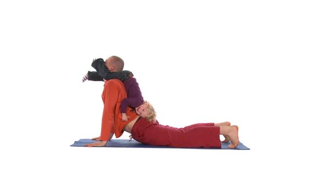 vídeos de stock e filmes b-roll de ws studio shot of father and daughter (2-3) doing yoga downward facing dog pose on exercise mat - cara para baixo