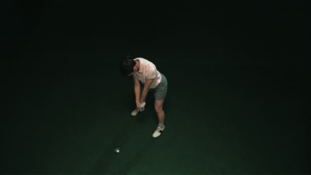 slo mo ws ha studio shot of female golf player teeing off - golf stock videos & royalty-free footage