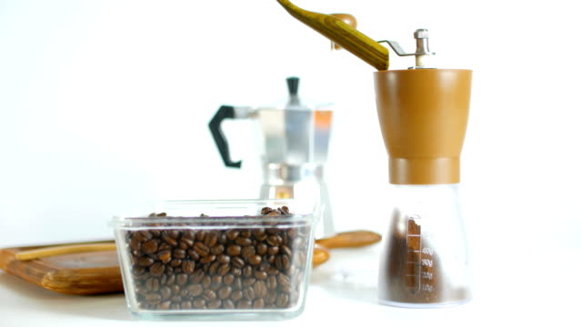 Studio Shot of Filling Coffee Beans into Manual Coffee Grinder