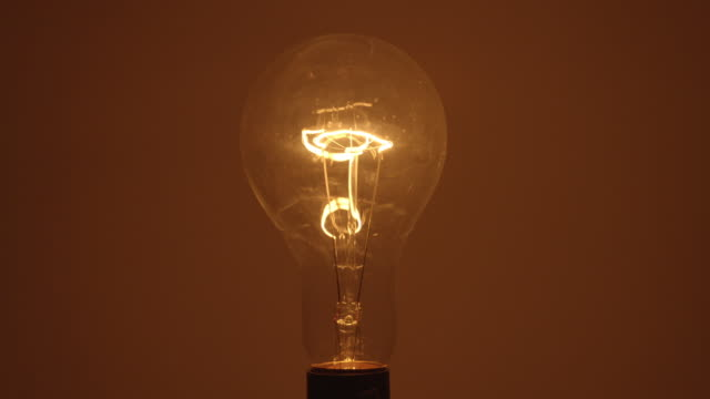 cu studio shot of flickering clear incandescent light bulb - filament stock videos & royalty-free footage