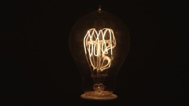 cu studio shot of flickering clear incandescent light bulb - incandescent bulb stock videos and b-roll footage