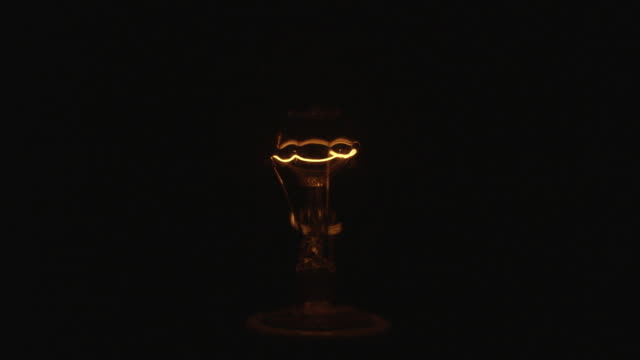 cu studio shot of flickering yellow incandescent light bulb - loopable moving image stock videos & royalty-free footage