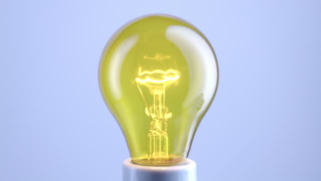 cu studio shot of flickering yellow incandescent light bulb - incandescent bulb stock videos and b-roll footage