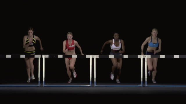 SLO MO WS Studio shot of four female athletes jumping hurdles