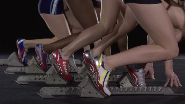 slo mo cu studio shot of four female runners at starting blocks, low section - human leg stock videos and b-roll footage
