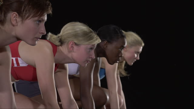 slo mo cu studio shot of four female runners at starting blocks - the competition stock videos and b-roll footage