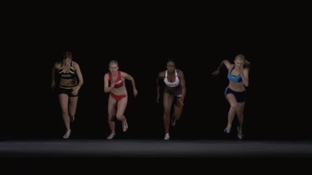 SLO MO WS Studio shot of four female runners racing