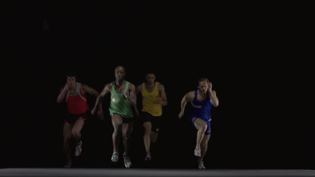 SLO MO WS Studio shot of four sprinters running towards camera