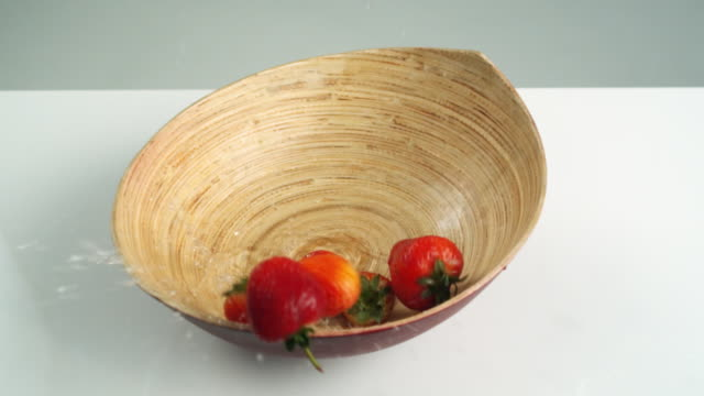 vidéos et rushes de slo mo ms studio shot of fresh strawberries falling into wooden bowl - groupe moyen d'objets