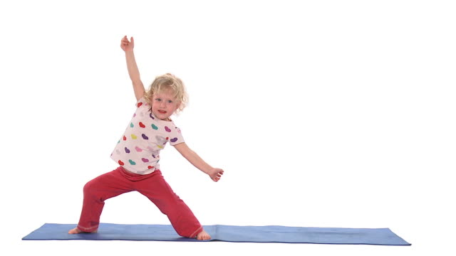 WS Studio shot of girl (2-3) doing yoga warrior II pose and clapping hands on exercise mat