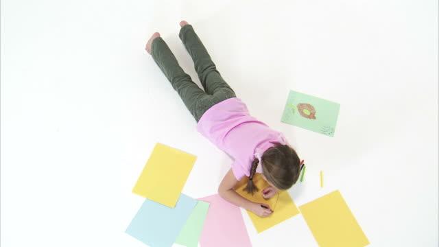 ws ha zi ms studio shot of girl (8-9) drawing on yellow paper / orem, utah, usa - korta ärmar bildbanksvideor och videomaterial från bakom kulisserna