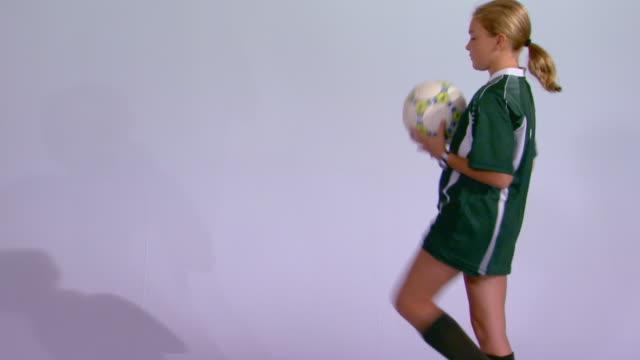 studio shot of girl in soccer uniform - jonglieren stock-videos und b-roll-filmmaterial