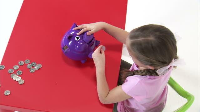 ms ha studio shot of girl (8-9) putting money into piggy bank at red table / orem, utah, usa - korta ärmar bildbanksvideor och videomaterial från bakom kulisserna