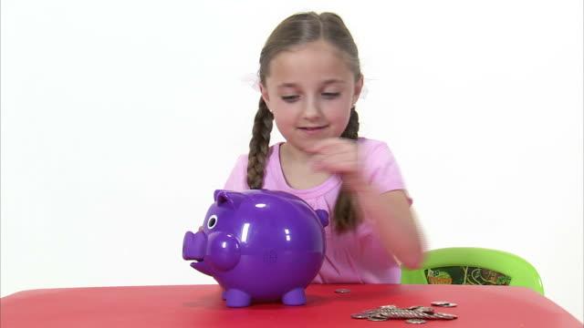 ms studio shot of girl (8-9) putting money into piggy bank at red table / orem, utah, usa - korta ärmar bildbanksvideor och videomaterial från bakom kulisserna