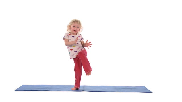 WS Studio shot of girl (2-3) standing on one leg and clapping hands on exercise mat