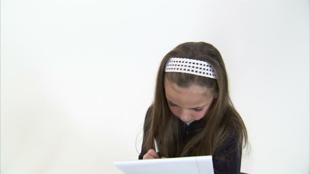 vídeos y material grabado en eventos de stock de ms cs studio shot of girl (8-9) writing in notebook / orem, utah, usa - cinta de cabeza
