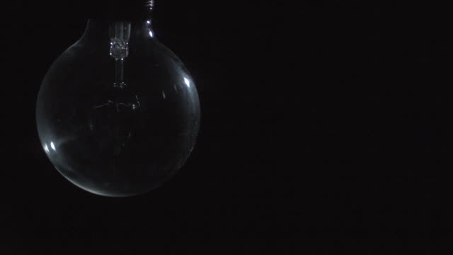 slo mo, cu, studio shot of glowing light bulb - light bulb stock videos and b-roll footage