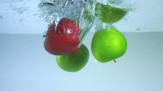 vídeos y material grabado en eventos de stock de slo mo cu studio shot of green and red apples falling into water - manzana