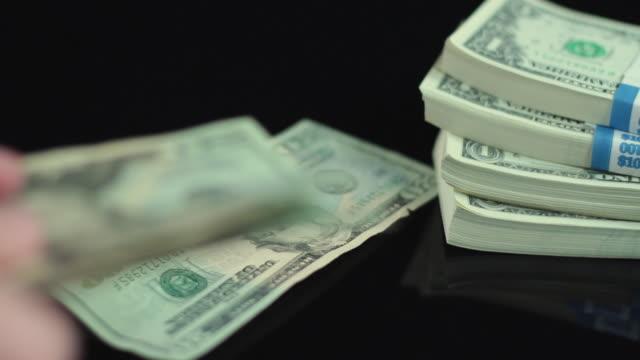 cu selective focus studio shot of hand counting dollars - us dollar geldschein stock-videos und b-roll-filmmaterial