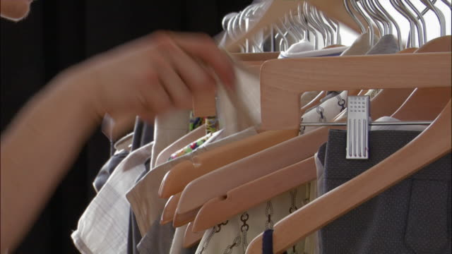 studio shot of hand rifling through clothes on rack / removing article of clothing - rack stock videos & royalty-free footage
