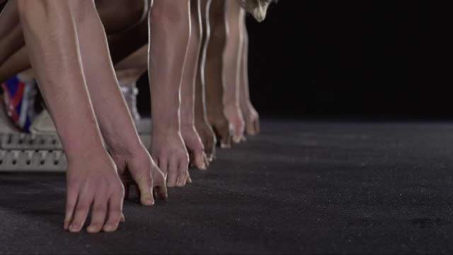 vídeos de stock, filmes e b-roll de slo mo cu studio shot of hands and feet of four female runners at starting blocks - concorrente