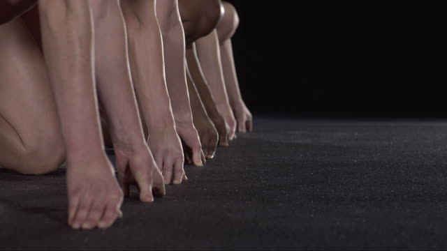 SLO MO CU Studio shot of hands and feet of four female runners at starting blocks