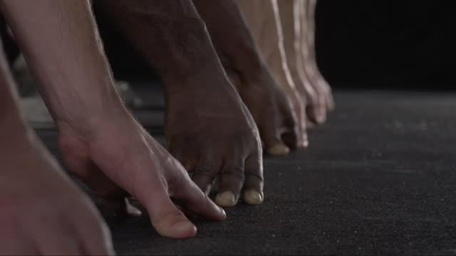 vídeos de stock e filmes b-roll de slo mo cu studio shot of hands and feet of four male runners at starting blocks - focagem