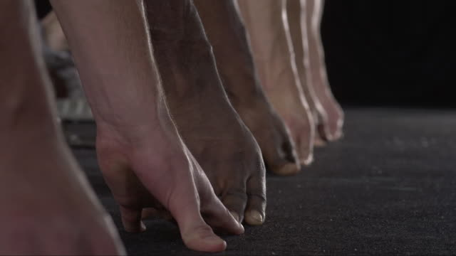 slo mo cu studio shot of hands and feet of four male runners at starting blocks - スタートライン点の映像素材/bロール