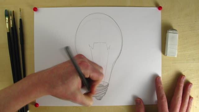 T/L CU Studio shot of hands painting light bulb