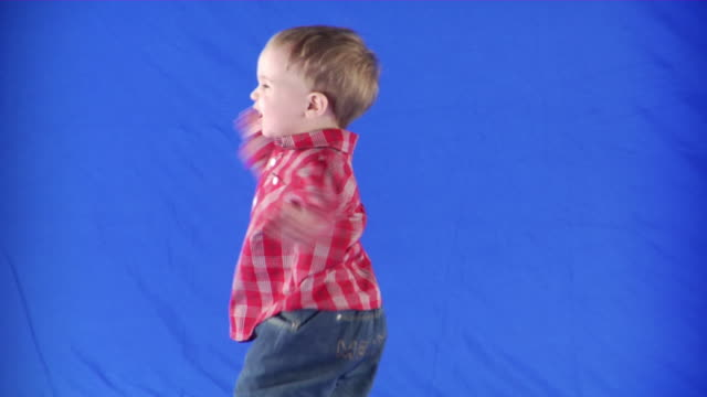 ms studio shot of happy baby boy (18-23 months) playing on blue screen - 18 23 months stock videos & royalty-free footage